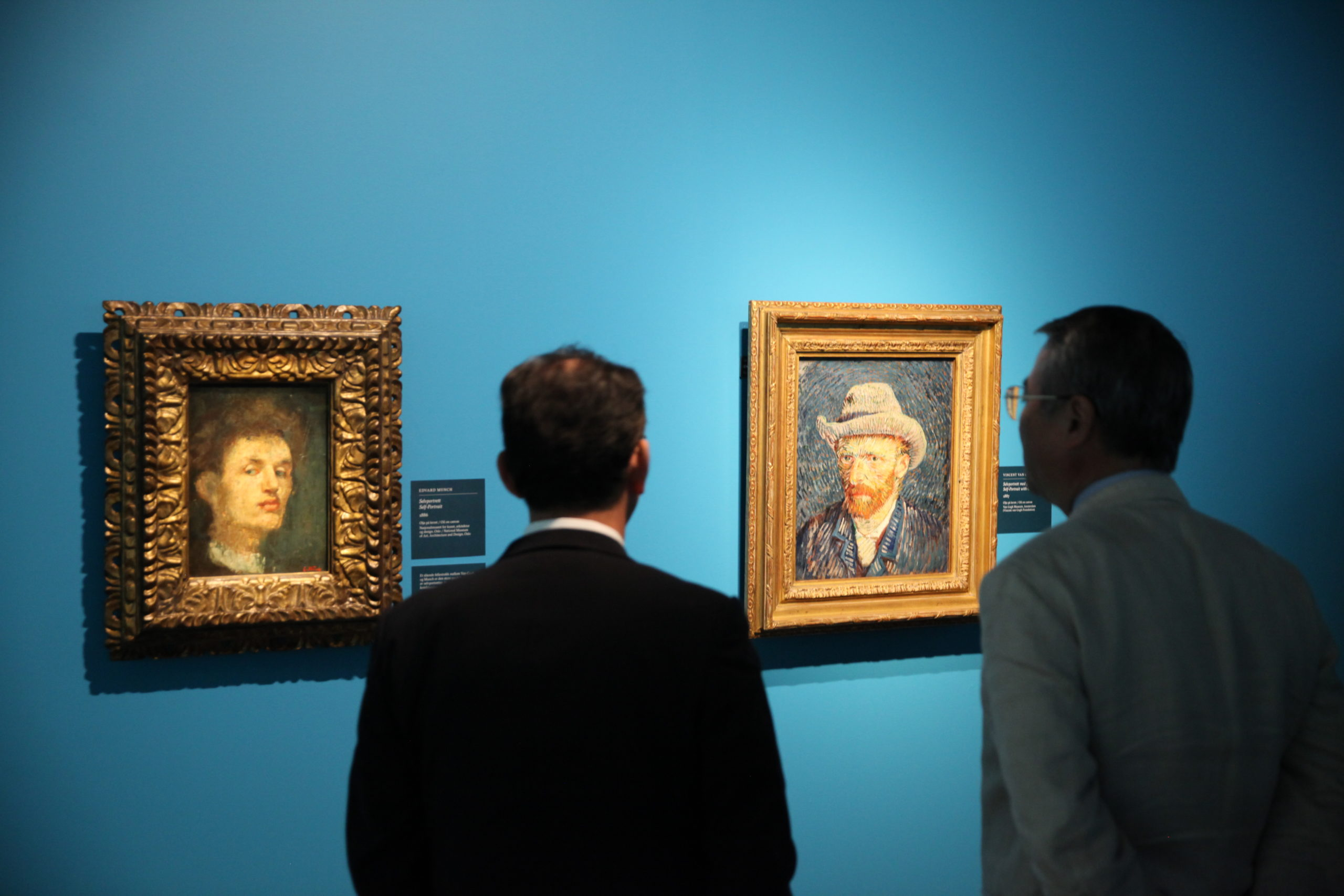 Visitors looking at Munch and van Gogh self portraits in Munchmuseet, 2015
